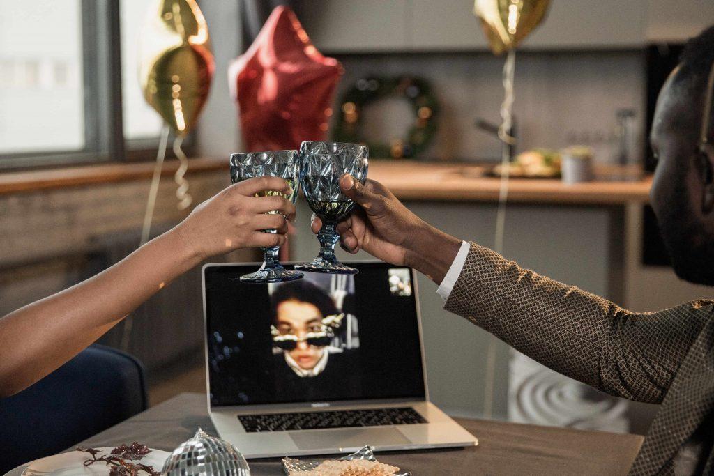 Eine Virutelle Party findet statt: Zwei Personen stoßen mit Ihren Gläsern an und halten einen Videoanruf