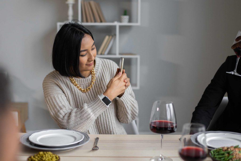 Eine Frau fotografiert einen Mann beim Abendessen
